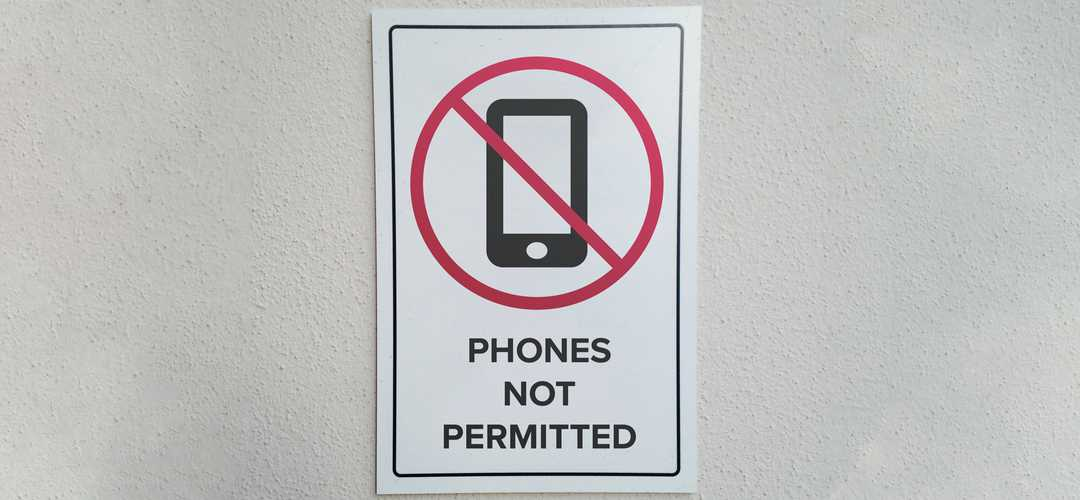A picture of a sign indicating that phones are not permitted