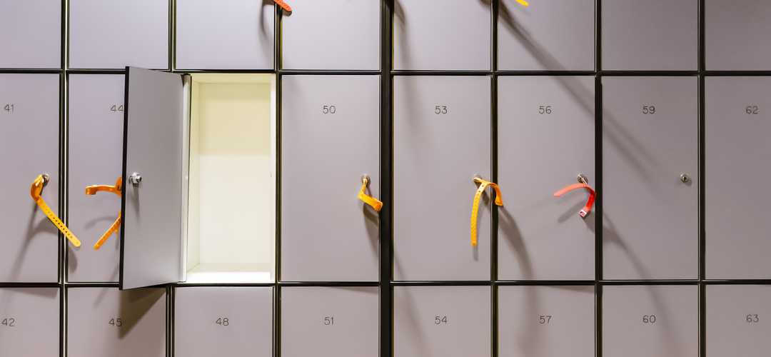A picture containing a wall of small lockers, used for phones
